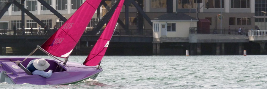 A brightly colored dinghy tacks in McCovey Cove